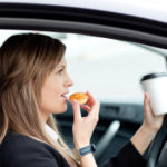 woman eating:drinking while driving